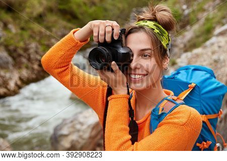 Happy Backpacker Poses Against Mountain River Flowning Through Green Forest, Makes Photos Of Wonderf