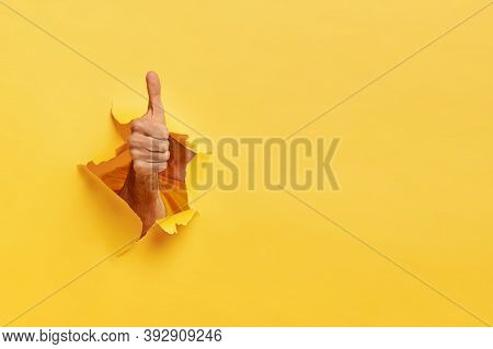 Unrecognizable Man Shows Like Gesture Through Torn Yellow Wall, Keeps Thumb Up, Says You Are Best, D