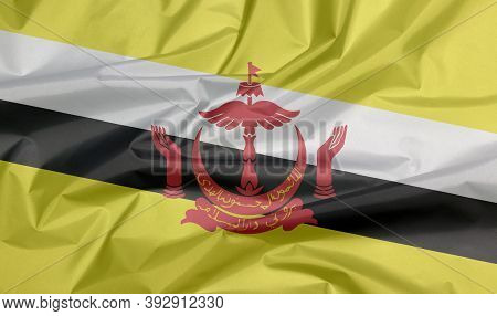 Fabric Flag Of Brunei Darussalam. Crease Of Brunei Flag Background, Red Crest On Yellow Field Cut By