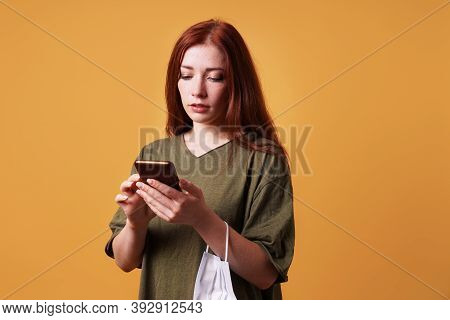 Young Woman Using Her Smartphone Or Mobile Phone While Face Mask Is Hanging Around Her Wrist