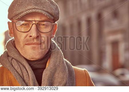 Close-up portrait of a handsome middle aged man in elegant clothes and glasses standing on the street. Men's beauty, fashion. Optics style.