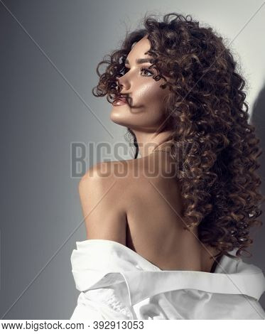 Beautiful young woman with curly hair posing, beauty model portrait, closeup. Beautiful sexy model girl in white cotton shirt. Flying hair, perfect make-up and manicure. Hairstyle. Vertical image