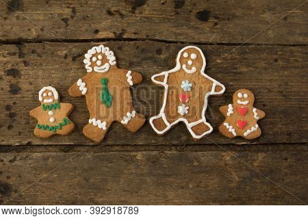 Edible gingerbread family with children on a rustic wooden board