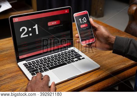Close Up Laptop And Smartphone Screen With Mobile App For Betting And Score. Male Hands Holding Devi