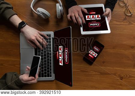 Close Up Laptop And Smartphone Screen With Mobile App For Online Casino Lottery. Male Hands Holding
