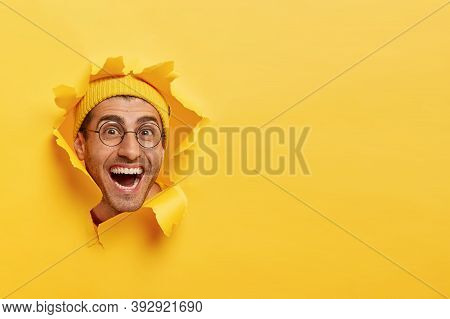 Amused Cheerful Young Man Looks Through Torn Paper Hole, Wears Yellow Hat And Round Spectacles, Smil