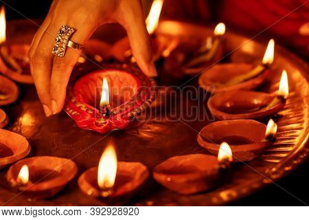 Happy Diwali Background. Closeup Image Of Female Hand Taking Lit Diya From A Puja Thali. Concept For