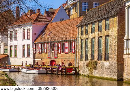 Bruges, Belgium - April 10, 2016: Scenic Cityscape With Medieval Houses, Cruise Boat Station With To