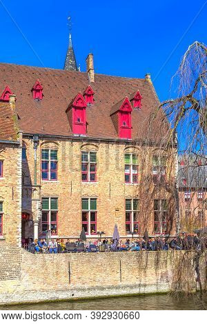Bruges, Belgium - April 10, 2016: Scenic Cityscape With Medieval Houses, Cafe With Tourists And Cana