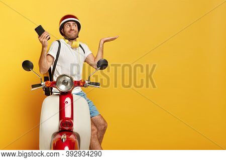 Confused Driver Of Motorcycle, Spreads Palms With Doubt, Holds Modern Cellular, Waits For Call, Ran