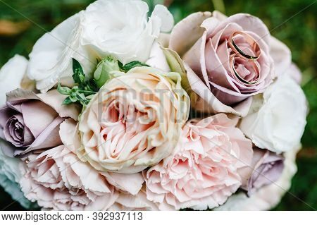 Wedding Rings Bride And Groom On The Background Bridal Bouquet With Gentle Pastel Flowers And Pink R