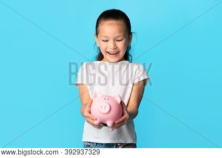 This Is My Own Savings. Portrait Of Smiling Asian Child Holding Pink Piggy Bank, Girl Standing With