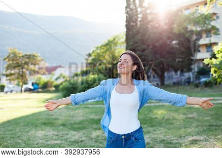 Young Woman Breathing Fresh Air In Park. Happy Girl Walking Alone In Nature And Enjoying Freedom. Ou