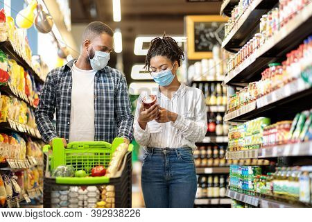 Grocery Shopping. African American Couple In Masks Buying Groceries Goods Walking With Shopping Cart
