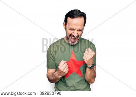 Middle age handsome man wearing t-shirt with revolutionary red star over white background celebrating surprised and amazed for success with arms raised and eyes closed