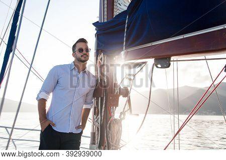 Man Traveling On Yacht. Young Sailor On Sailing Boat. Traveler Enjoying Sea Adventure, Freedom. Summ
