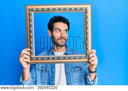 Young hispanic man holding empty frame smiling looking to the side and staring away thinking.