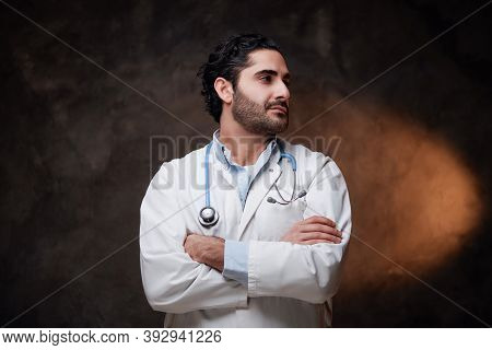 Bearded And Cheerful Doctor In Labcoat With Stethoscope On His Neck Poses In Dark Background.