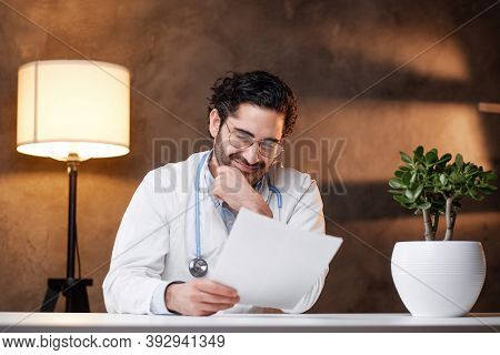 Focused And Serious Doctor With Beard In White Labcoat Sitting At Table In Dark Background.