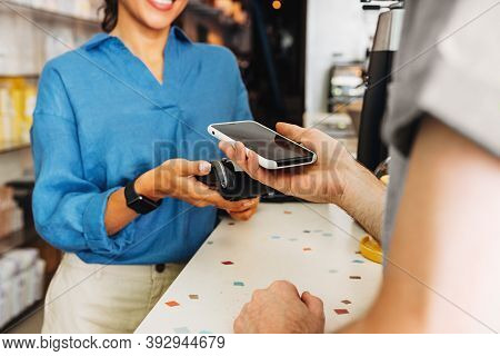Hand Of A Customer At A Cafe Paying His Bill Using A Mobile Phone. Female Entrepreneur Holding A Pos