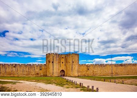 The medieval port city of Aigues-Mortes. Antique walls and picturesque powerful gates surround the ancient city. Around the walls are green lawns. The concept of historical and photo tourism