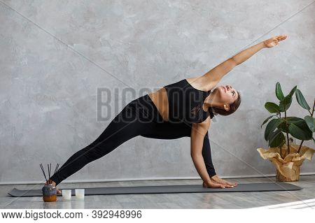 Portrait Of Sporty Young Woman Doing Exercises On Yoga Lesson At Home. Beautiful Girl Practicing Sid