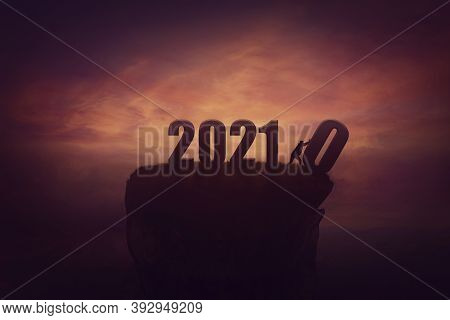 Silhouette Of A Determined Man On The Top Of A Cliff Over Sunset, Announcing The New 2021 Year Comin