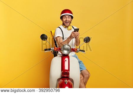 Photo Of Overjoyed Surprised Man Delivers Something, Has Rest During Driving Bike, Carries Rucksack,