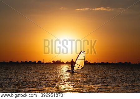 Silhouette Of A Woman Windsurfer On The Waves Of The Bay At Sunset