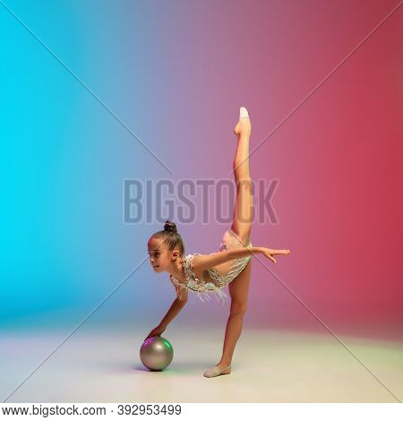 Energy. Little Caucasian Girl, Rhytmic Gymnast Training, Performing Isolated On Gradient Blue-red St