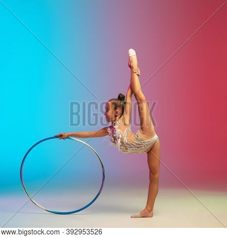 Movement. Little Caucasian Girl, Rhytmic Gymnast Training, Performing Isolated On Gradient Blue-red