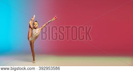 Flyer. Little Caucasian Girl, Rhytmic Gymnast Training, Performing Isolated On Gradient Blue-red Stu