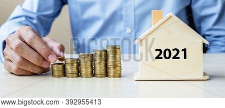 Business Man Hand Putting Golden Coin On Growing Money Stairs With 2021 Wood Home. Happy New Year Bu