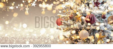 Christmas Tree With Decorations And Glitter. Shiny Lights In Gold Background