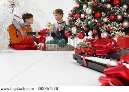 Merry Christmas And Happy Holidays, Children Play Guitar And Tambourine Near The Christmas Tree With
