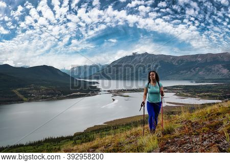 Adventurous Girl Hiking Up The Nares Mountain During A Cloudy And Sunny Day. Taken Near Whitehorse,
