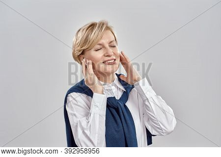 Portrait Of Elegant Middle Aged Caucasian Woman Wearing Business Attire, Adjusting Her Earbuds, Smil
