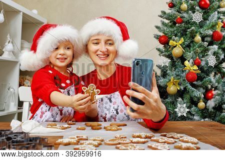 Mother And Daughter Prepare Christmas Ginger Cookies And Decorate It With Icing For A Happy Holidays