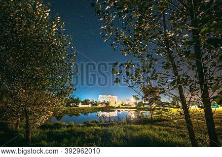 Night Sky Over River Lake Near Residential Houses. Night Starry Sky Above Lake River With Bright Sta