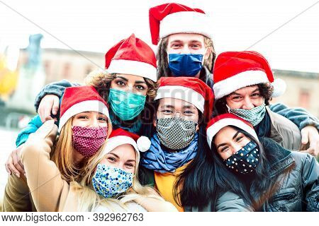 Multiracial Friends Taking Selfie Wearing Face Mask And Santa Hat - New Normal Christmas Holiday Con
