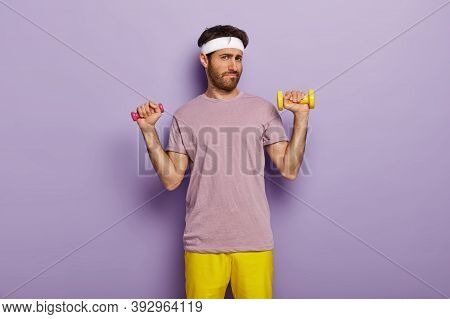 Young Man Looks Unpleasantly At Camera, Raises Two Dumbbells, Has Fitness Exercise, Trains Muscles O
