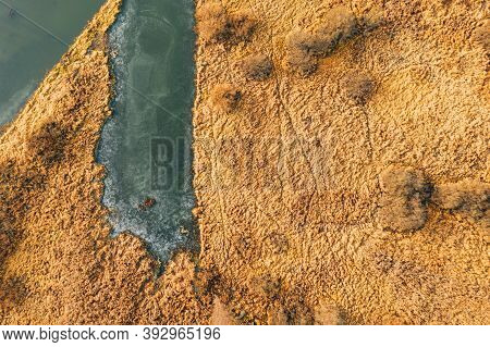 Aerial View Of Dry Grass And Partly Frozen River Landscape In Late Autumn Day. High Attitude View. M