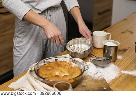 Tasty Apple Pie On A Oaken Wood Table With A Ingredients. Woman In A Gray Pajama Cooking A Delicious