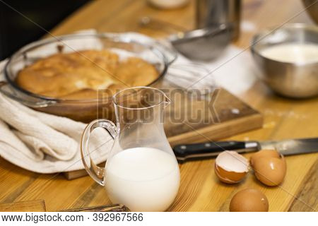 Tasty Apple Pie On A Oaken Wood Table With A Ingredients. Cooking A Delicious Apple Pie On A Kitchen
