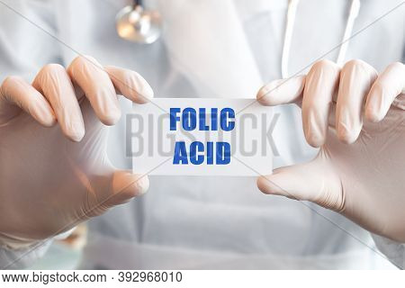 Doctor Holding A Card With Text Folic Acid