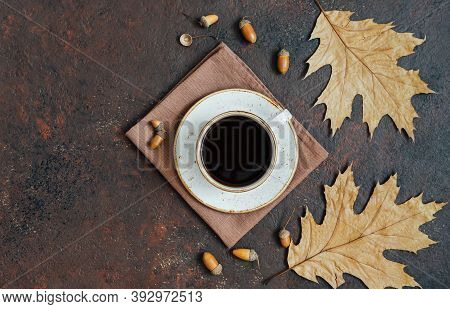 Coffee In A White Cup With Leaves And Acorns On A Brown Background. Acorn Coffee. Space For Text. To