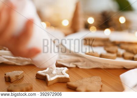 Hands Decorating Baked Christmas Star Cookie With Sugar Frosting. Family Christmas Time