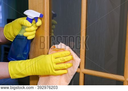Hands In Gloves With A Rag And Detergent Clean The Glass On The Doors. House Cleaning