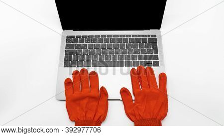 Red Protective Gloves Lie Next To The Laptop, Close Up View. Concept Of Network Communications, Onli