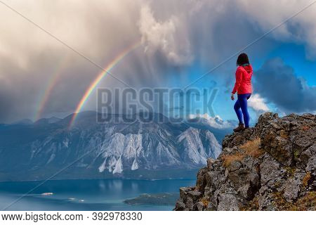 Adventurous Girl Hiking Up The Nares Mountain During A Cloudy And Sunny Day With Rainbow. Taken Near